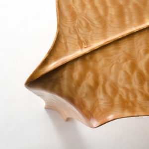 Close-up view of the signature curved leg and raised leaf design on our hand-carved Kvalheim Coffee Table