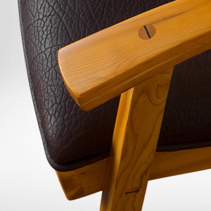 Close-up view of the handmade upholstery and handcarved accents on the Tashjian Chair