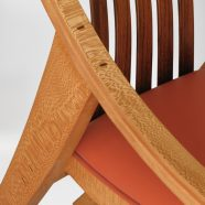 Close-up view of the hand carved custom curve armrest on the Elrod Chair