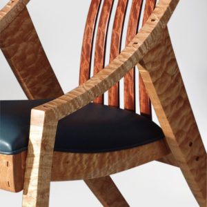 Close-up of the curved armrest and fluted slats on our custom Elrod Chair w/ hand-sewn upholstery