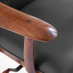 Close-up view of the hand carved armrest on our custom office chair, The McCorkle Chair