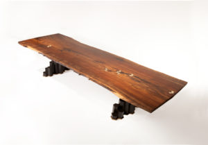 Handmade Filip dining table crafted from California walnut w/ hand-carved basalt base and bronze inlay