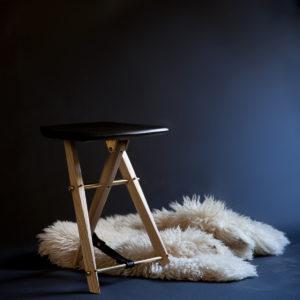 The custom-made Langhorne Stool photographed with sheepskin blanket